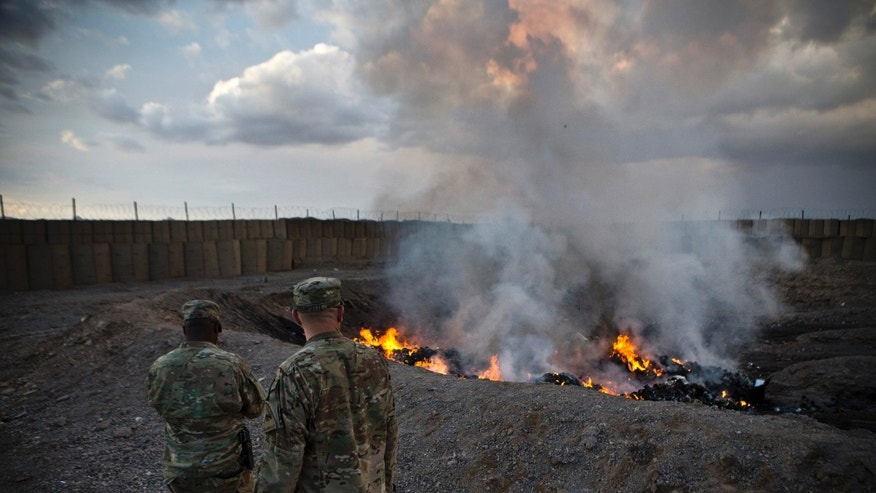 FILE -- U.S. Army soldiers watch garbage burn in a burn-pit at Forward Operating Base Azzizulah in Maiwand District, Kandahar Province, Afghanistan, February 4, 2013. REUTERS/Andrew Burton