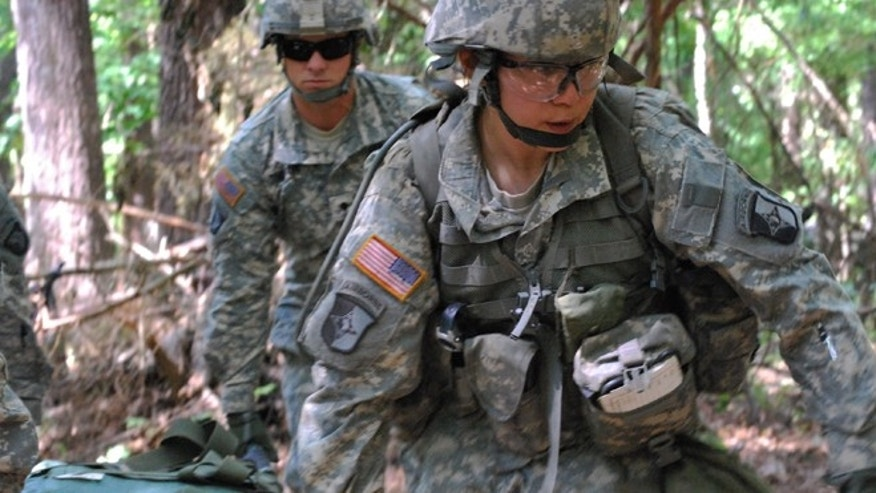 FILE - May 9, 2012: Capt. Sara Rodriguez, 26, of the 101st Airborne Division, carries a litter of sandbags during the Expert Field Medical Badge training at Fort Campbell, Ky. (AP Photo/Kristin M. Hall)