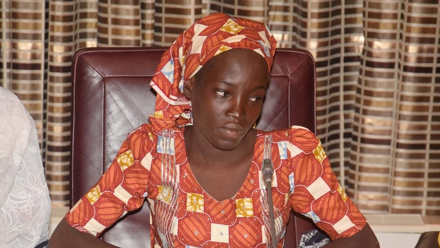 Amina Ali, the rescue Chibok school girl, sits during a meeting with Nigeria's President Muhammadu Buhari at the Presidential palace in Abuja, Nigeria, Thursday, May. 19, 2016. The first Chibok teenager to escape from Boko Haram's Sambisa Forest stronghold was flown to Abuja on Thursday and met with Nigeria's president, even as her freedom adds pressure on the government to do more to rescue 218 other missing girls. (AP Photo/Azeez Akunleyan)
