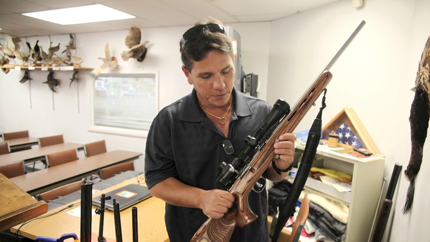 FILE - May 10, 2016: Jerry Ilo holds a gun that he uses to teach the Hawaii Department of Natural Resources hunter education training course in a classroom in Honolulu. Ilo was one of several Hawaii residents to speak out against a bill passed by lawmakers to allow Hawaii gun owners to be registered in a federal database that will automatically notify police if an island resident is arrested anywhere else in the country.