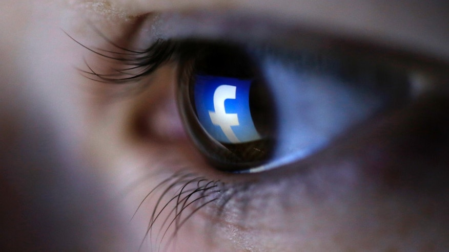 FILE -- March 13, 2015: A picture illustration shows a Facebook logo reflected in a person's eye.
