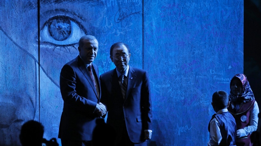 United Nations Secretary General Ban Ki-moon, centre and Turkish President Recep Tayyip Erdogan, pose in front of a graffiti at the closing ceremony of the World Humanitarian Summit in Istanbul, Tuesday, May 24, 2016. World leaders and representatives of humanitarian organisations from across the globe gathered in Istanbul on May 23-24, 2016 for the first World Humanitarian Summit, focused on how to reform a system many judge broken. (AP Photo/Lefteris Pitarakis)