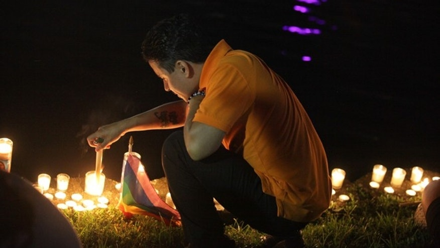 Hector Silva lights a candle along Lake Eola in Orlando, Sunday, June 12, 2016. The New York native made Orlando home in 2004 and came to the vigil for the victims of the Pulse night club tragedy.