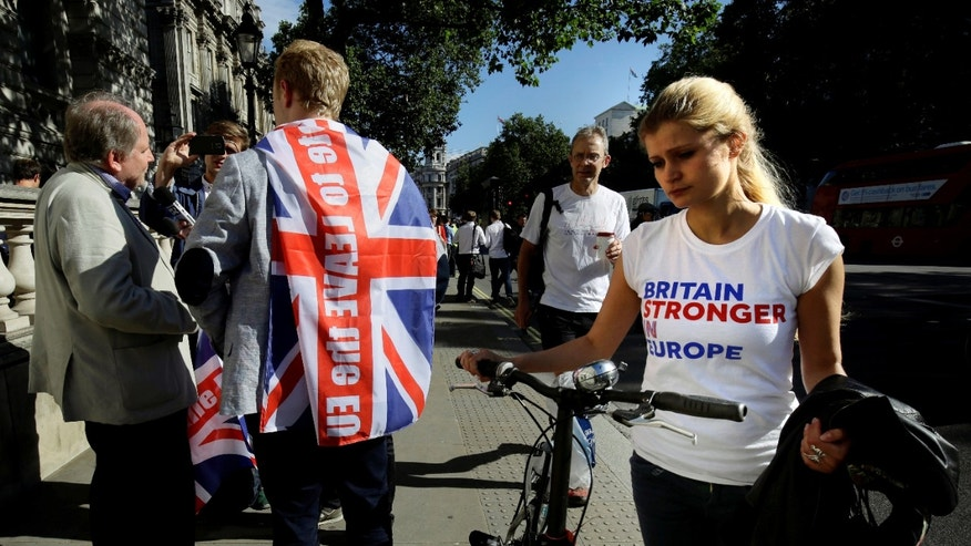 June 24, 2016: A vote remain supporter walks past a vote leave supporter outside Downing Street in London.