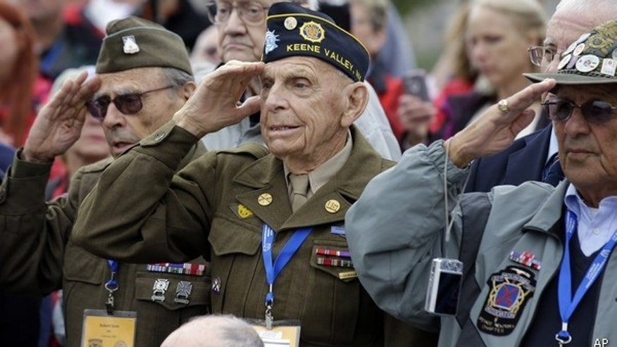 FILE -- World War II 10th Mountain Division veteran Charles W. Smith, center, from Plattsburgh, N.Y., salutes with others, during the singing of the National Anthem at the WWII Memorial in Washington.