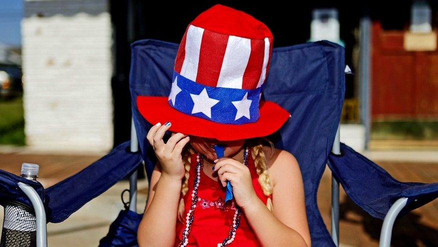 FILE -- Hannah Hargis enjoys a snack as she watches the LibertyFest Fourth of July Parade in Edmond, Okla.
