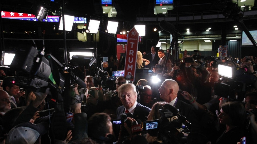 "Republican 2016 U.S. presidential candidate businessman Donald Trump is surrounded by news media in the ""spin room"" after the conclusion of the first official Republican presidential candidates debate of the 2016 U.S. presidential campaign in Cleveland, Ohio, August 6, 2015."