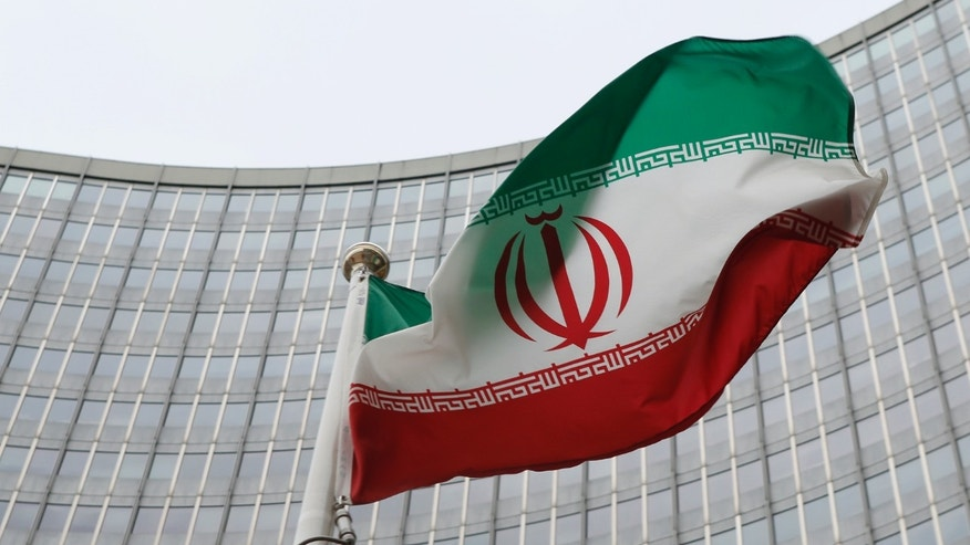 FILE --  January 15, 2016: An Iranian flag flutters in front of the International Atomic Energy Agency (IAEA) headquarters in Vienna, Austria.