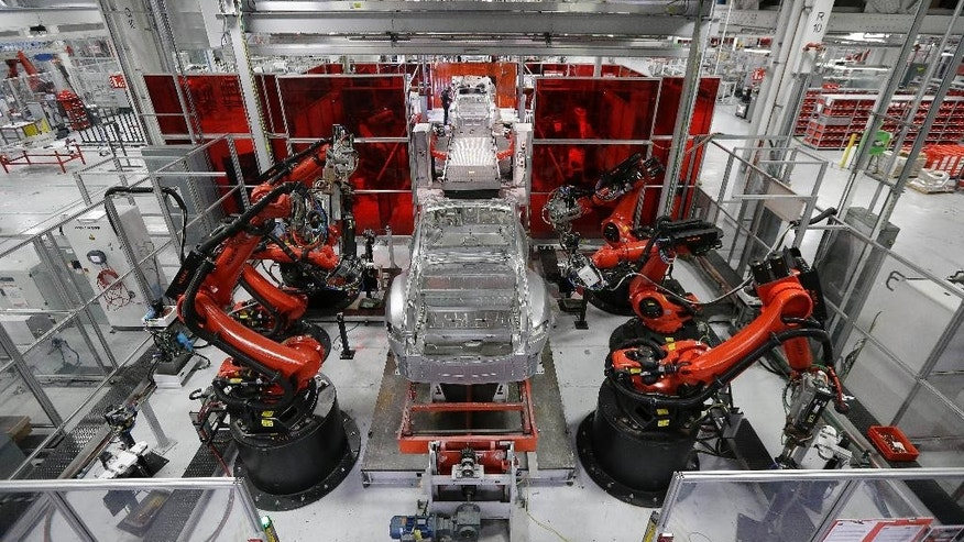 FILE - May 14, 2015: Kuka robots work on Tesla Model S cars in the Tesla factory in Fremont, Calif.
