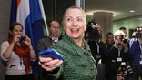 FILE - In this Dec. 8, 2011, file-pool photo, then-Secretary of State Hillary Rodham Clinton hands off her mobile phone after arriving for a meeting in The Hague, Netherlands. A federal judge says he may order Democratic presidential front-runner Hillary Clinton to testify under oath about whether she used a private email server as secretary of state to evade public records disclosures.  (AP Photo/J. Scott Applewhite, Pool, File)