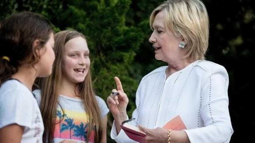 Democratic presidential candidate Hillary Clinton speaks with neighborhood children as she signs a book for them following a fundraiser at a private home in Sagaponack, N.Y., Tuesday, Aug. 30, 2016. (AP Photo/Andrew Harnik)