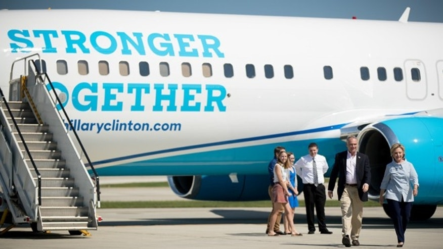 Democratic presidential candidate Hillary Clinton, right, accompanied by Democratic vice presidential candidate, Sen. Tim Kaine, D-Va., second from right, walks across the tarmac as Clinton arrives at Cleveland Hopkins International Airport in Cleveland, Ohio, Monday, Sept. 5, 2016, after traveling from Westchester County Airport in White Plains, N.Y. (AP Photo/Andrew Harnik)