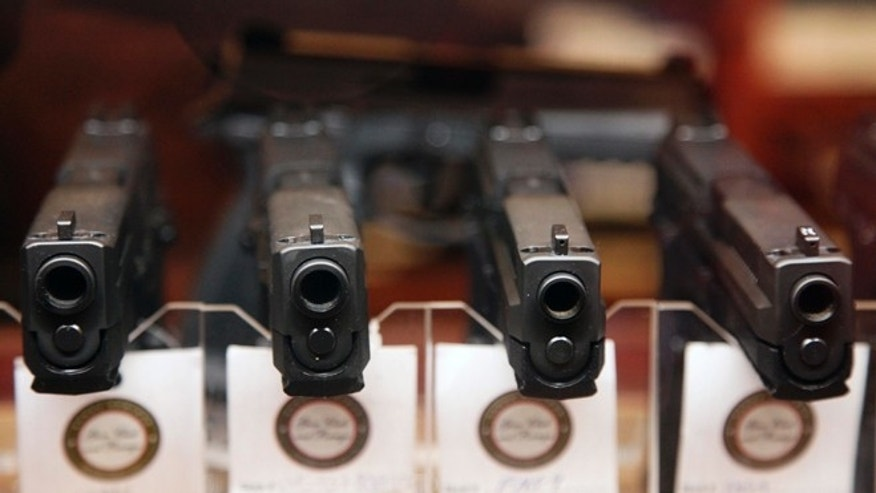 FILE- Handguns are displayed in the sales area of Sandy Springs Gun Club and Range, in Sandy Springs, Ga