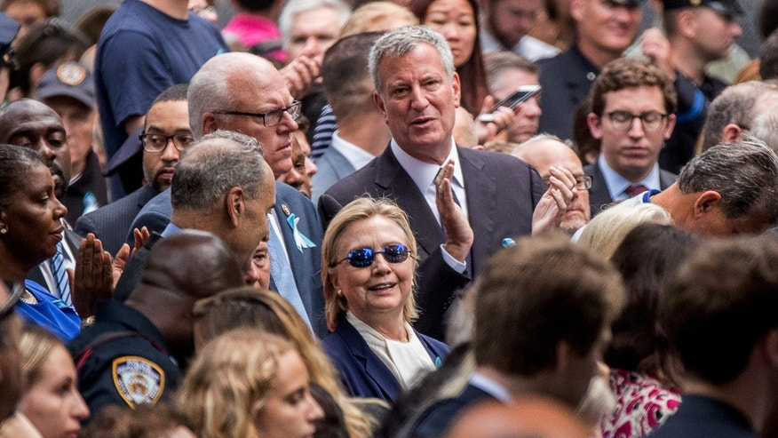Democratic presidential candidate Hillary Clinton, center, accompanied by Sen. Chuck Schumer, D-N.Y., center left, Rep. Joseph Crowley, D-N.Y., second from left, and New York Mayor Bill de Blasio, center top, attends a ceremony at the Sept. 11 memorial, in New York, Sunday, Sept. 11, 2016.