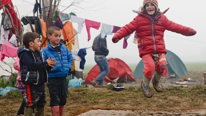 FILE- Migrant children play jumping on a muddy mattress at the northern Greek border point of Idomeni, Greece, Friday, March 18, 2016.