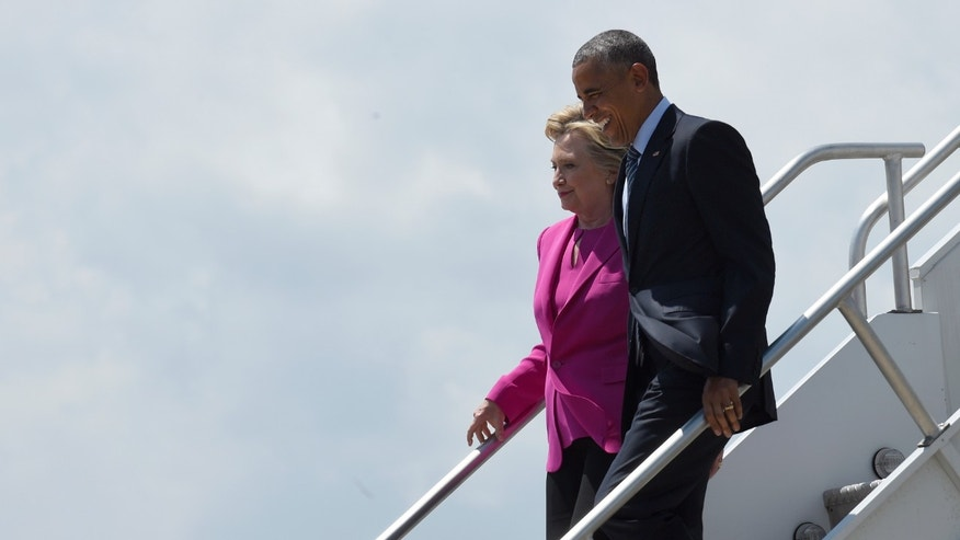FILE -- July 5, 2016: President Obama and Democratic presidential candidate Hillary Clinton walk down the steps of Air Force One after arriving at North Carolina Air National Guard Base in Charlotte, N.C