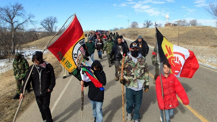 FILE - In this Feb. 27, 2014 photo, more than 100 people walk to Wounded Knee during the liberation anniversary of the famous massacre on the Pine Ridge Indian Reservation in South Dakota.