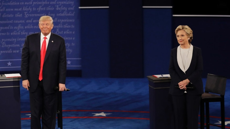Republican presidential nominee Donald Trump and Democratic presidential nominee Hillary Clinton listen to a question during the second presidential debate at Washington University in St. Louis, Sunday, Oct. 9, 2016.