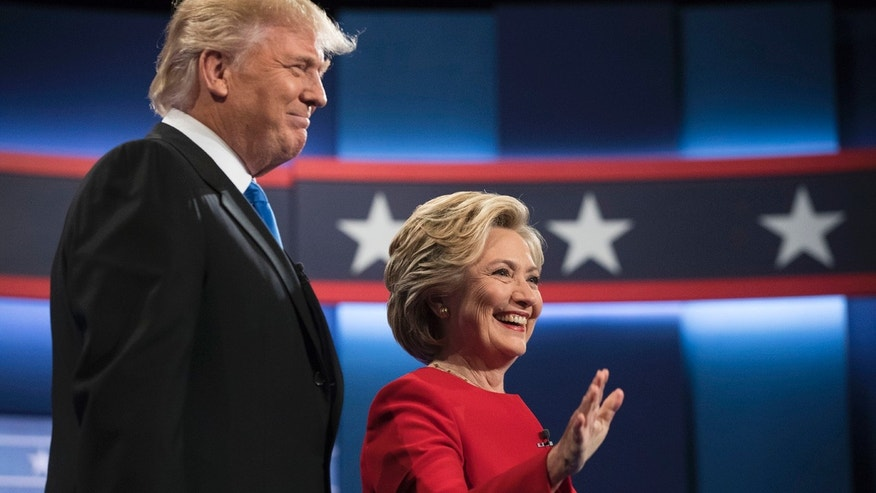 Democratic presidential nominee Hillary Clinton, right, stands with Republican presidential nominee Donald Trump at the start of the presidential debate at Hofstra University in Hempstead, N.Y., (AP Photo/Matt Rourke)