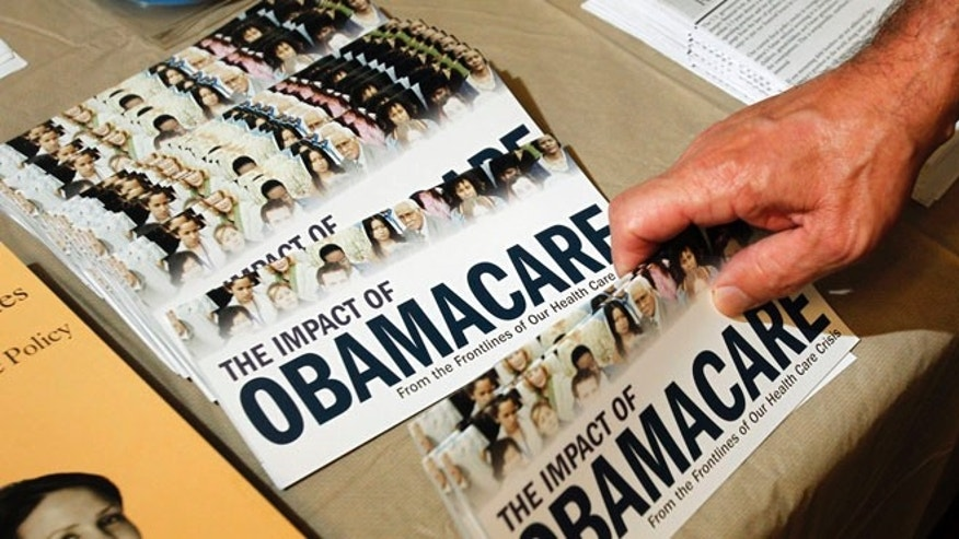"FILE - A Tea Party member reaches for a pamphlet titled ""The Impact of Obamacare""."