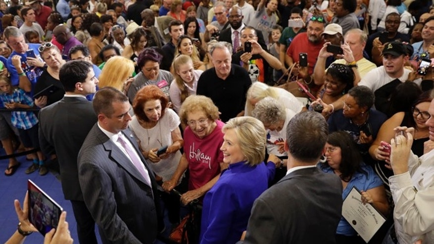 FILE - Democratic presidential candidate Hillary Clinton meets with attendees during a campaign stop at the Frontline Outreach Center in Orlando, Fla., Wednesday, Sept. 21, 2016.
