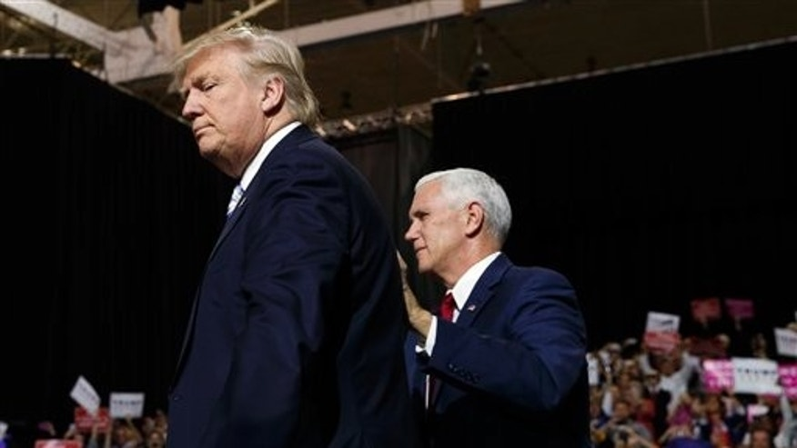 Republican presidential candidate Donald Trump, left, is accompanied by his running mate, Governor of Indiana, Mike Pence, during a campaign rally in Cleveland, Ohio, on Saturday October 22, 2016.