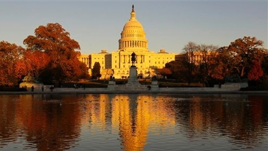 FILE - The US Capitol is bathed in the setting sun and seen in the reflecting pool on Capitol Hill in Washington, Friday, Nov. 12, 2010.