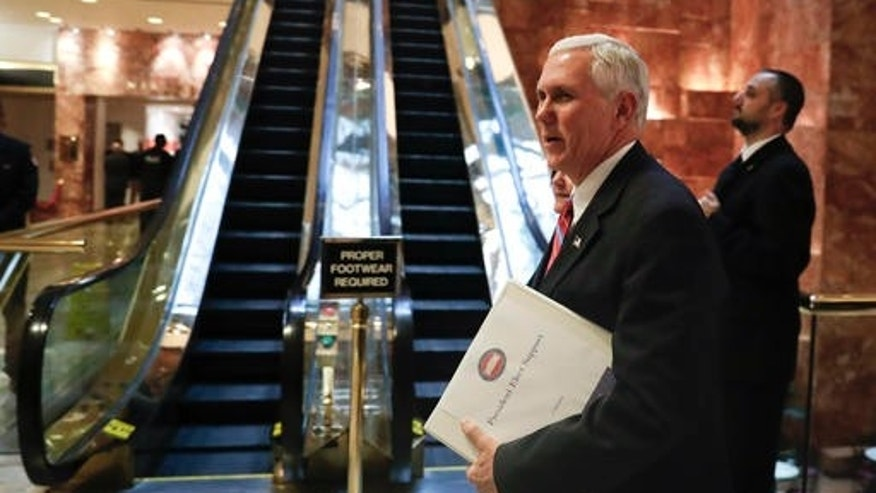 Vice President-elect Mike Pence carries a briefing binder as he arrives at Trump Tower, Tuesday, Nov. 15, 2016, in New York.