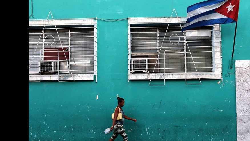 A woman walks under a Cuban flag in Santiago de Cuba.