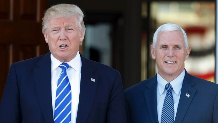 FILE -- President-elect Donald Trump and Vice President-elect Mike Pence pause for photographs as they arrive at the Trump National Golf Club Bedminster clubhouse in Bedminster, N.J., Saturday, Nov. 19, 2016.