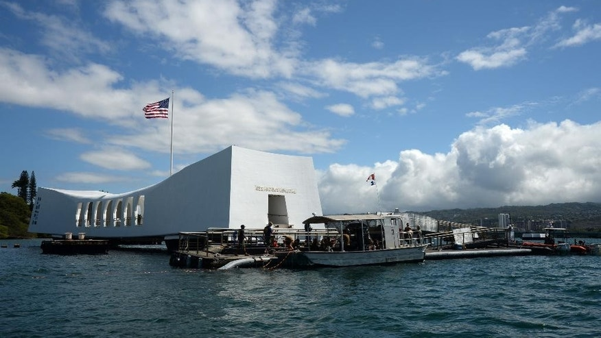 FILE -- In this Wednesday, June 3, 2015, photo provided by the U.S. Navy, sailors work to repair the floating dock next to the USS Arizona Memorial in Pearl Harbor, Hawaii.