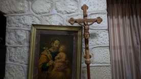 In this photo taken Sunday, May 18, 2014, a wooden cross and a painting is seen at the office of Father Ibrahim Shomali, the parish priest of Beit Jala and leads meditating efforts between local Christians and Palestinian Christian emigre families who abandoned their homes, in order to keep Christian properties among Christians, at the Annunciation Latin Church, in the West Bank town of Beit Jala. Pope Francis will be arriving this weekend to the land where Christianity was born, and where Christians are disappearing. The Christian community in the Holy Land is one of the oldest in the world. But it has dwindled to around 2 percent of the population today, as economic hardship, violence and the bitter realities of the Israeli-Palestinian conflict have sent them searching for better opportunities overseas. (AP Photo/Nasser Nasser)