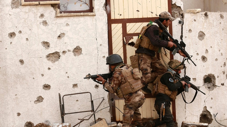 Soldiers with Iraq's elite counterterrorism forces secure houses and streets during fighting against Islamic State militants to regain control of the eastern neighborhoods of Mosul, Iraq, Tuesday, Dec. 13, 2016.
