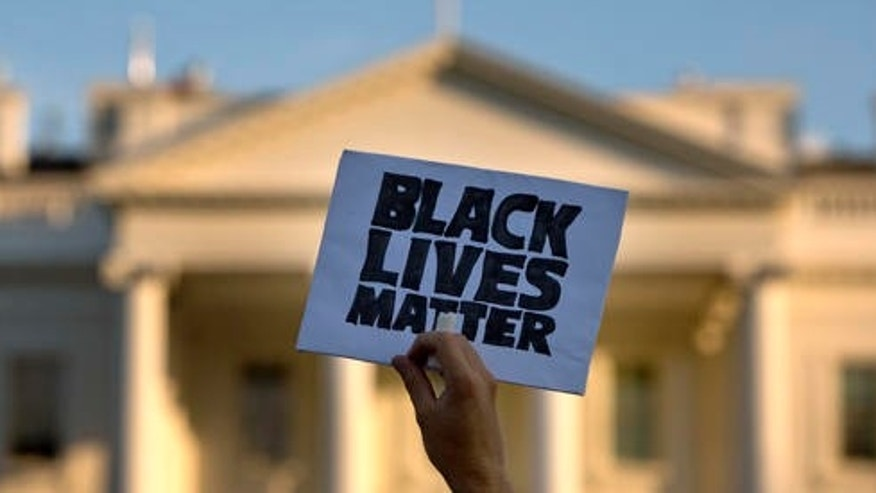 "FILE - In this July 8, 2016 file photo, a man holds up a sign saying ""black lives matter"" during a protest of shootings by police, at the White House in Washington."