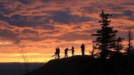 Three couples enjoy the spring equinox sunset over Turnagain Arm from Beluga Point on Saturday, March 21, 2015, in Anchorage, Alaska. The high temperature Saturday reached a high of 42 degrees, 7 degrees above the normal high, according to the National Weather Service.  (AP Photo/Dan Joling)