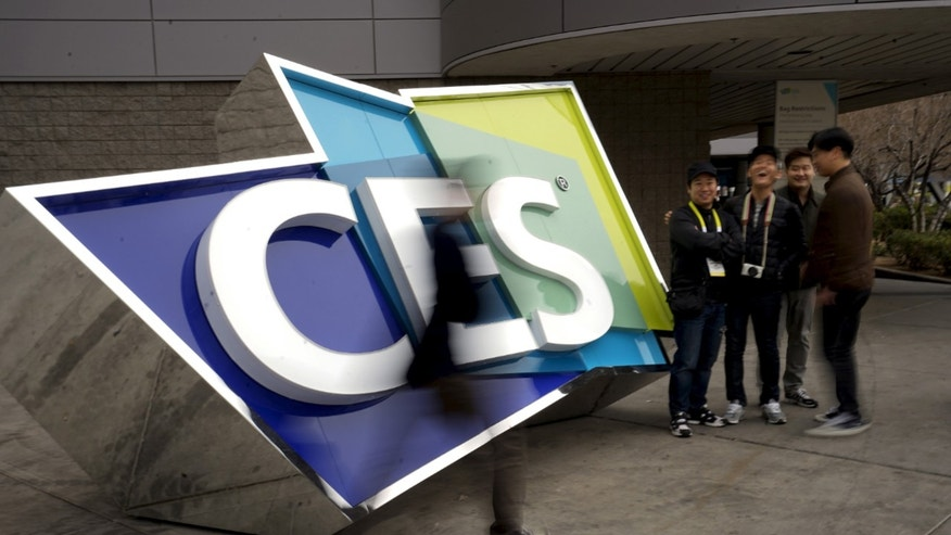FILE -- Attendees pass by a sign outside the Consumer Electronics Show in Las Vegas, January 5, 2016.