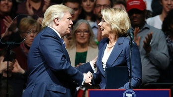 President-elect Donald Trump shakes hands with his pick for Education Secretary Betsy DeVos during a rally, in Grand Rapids, Mich., Friday, Dec. 9, 2016. (AP Photo/Paul Sancya)