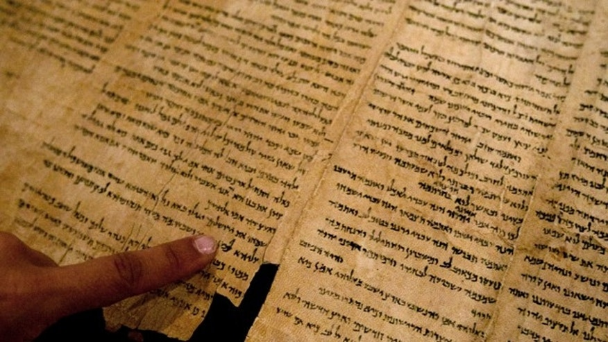 "FILE -- An Israel Museum worker points at the word ""Jerusalem"" written in a part of the Isaiah Scroll, one of the Dead Sea Scrolls."