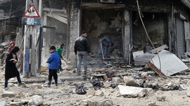 In this Jan. 20, 2017 photo, Syrian children remove rubble in the once rebel-held Bustan al-Qasr neighborhood in eastern Aleppo, Syria. Aleppo, Syria's largest city, was widely brought to ruin by years of war, and now with Russia and Turkey leading peace efforts, international officials say it is time to start talking about rebuilding Aleppo and other cities. But there are few answers on how to do it, with the world reluctant to donate the billions needed and a political settlement in the war still uncertain and far off. (AP Photo/Hassan Ammar)