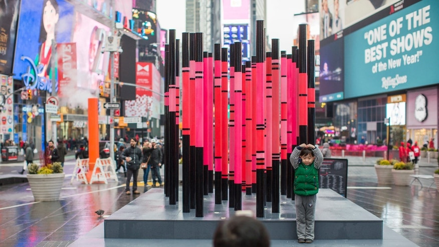A visitor to New York's Times Square poses for a photo with an art installation.