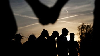 """In this Sunday April 10, 2016 photo, youths hold hands for a prayer during a gathering at sunset outside the Christian Fellowship Church in Benton, Ky. Nearly a quarter of Americans say they no longer affiliate with a faith tradition. It's the highest share ever recorded in surveys, indicating the stigma for not being religious has eased, even in heavily evangelical areas. Americans who say they have no ties to organized religion, dubbed """"nones,"""" now make up about 23 percent of the population, just behind evangelicals, who comprise about 25 percent, according to the Pew Research Center. (AP Photo/David Goldman)"""