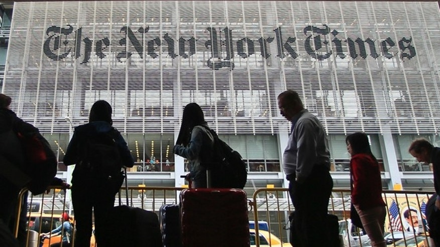 May 14, 2014: Pedestrians wait for cabs across the street from The New York Times in New York. (AP)