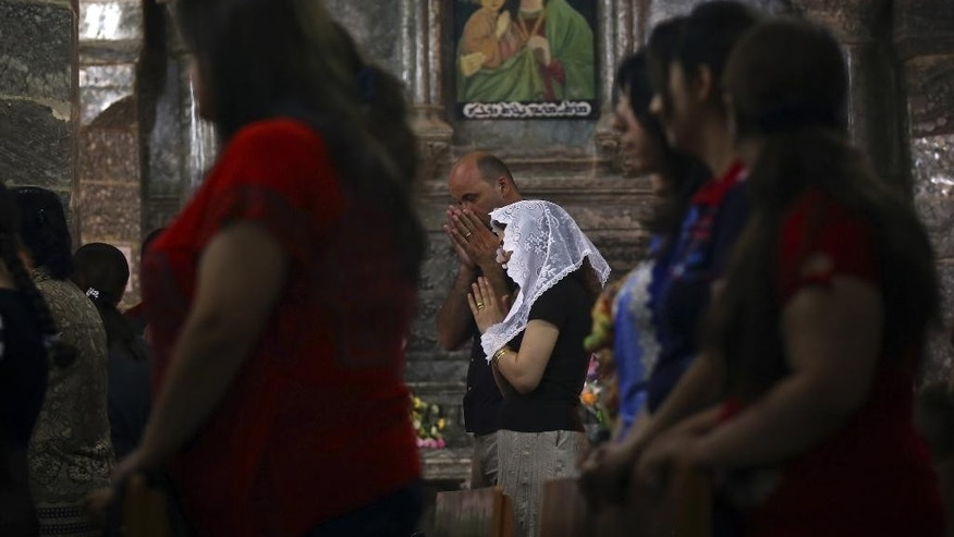 FILE -- June 15, 2014: Iraqis attend Mass at the Chaldean Church of the Virgin Mary of the Harvest, in al-Qoush, set in the seventh century Saint Hormoz monastery built into a hill overlooking Alqosh, a village of some 6,000 inhabitants about 50 kilometers (31 miles) north of Mosul, northern Iraq.