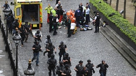 """Armed police walk past emergency services attending to injured people on the floor outside the Houses of Parliament, London, Wednesday, March 22, 2017.  London police say they are treating a gun and knife incident at Britain's Parliament """"as a terrorist incident until we know otherwise."""" The Metropolitan Police says in a statement that the incident is ongoing. It is urging people to stay away from the area. Officials say a man with a knife attacked a police officer at Parliament and was shot by officers. Nearby, witnesses say a vehicle struck several people on the Westminster Bridge.  (Stefan Rousseau/PA via AP)."""