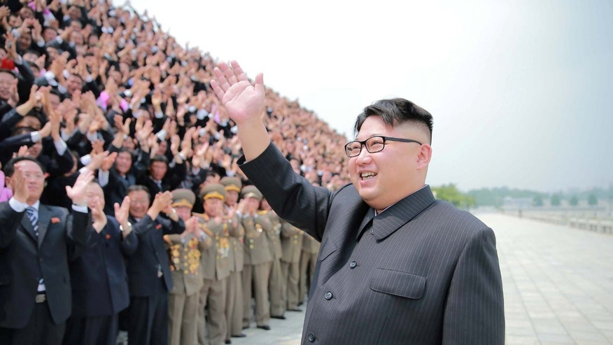 FILE -- North Korean leader Kim Jong Un waves as he participates in a photo session with officials who are committed to the success of the test-fire of surface-to-surface medium long-range strategic ballistic missile Hwasong-10.