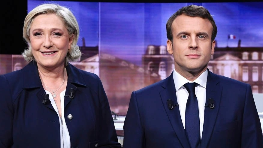 FILE -- May 3, 2017: Marine Le Pen, left, and Emmanuel Macron, pose prior to the start of a televised debate in La Plaine-Saint-Denis, north of Paris, France.