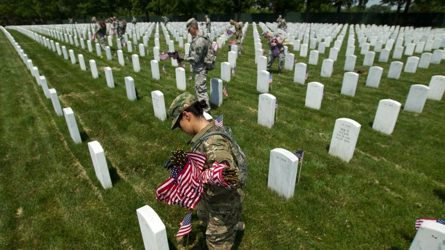 Members of the Old Guard with the Washington Memorial in the back, place flags in front of every headstone at Arlington National Cemetery in Arlington, Va., Thursday, May 26, 2016. Soldiers were to place nearly a quarter of a million American flags at the cemetery as part of a Memorial Day tradition. ( AP Photo/Jose Luis Magana)