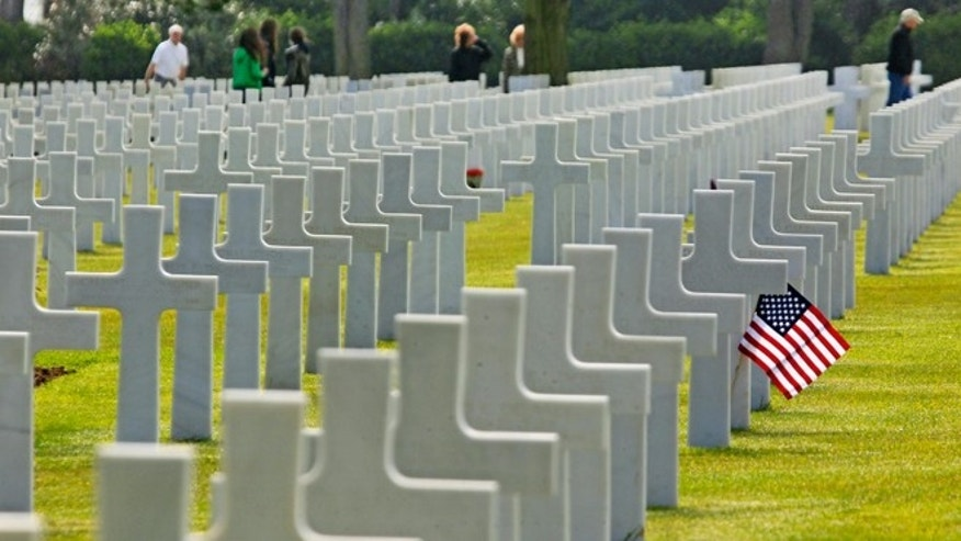 FILE -- June 6, 2013: Visitors walk among the 9,387 graves at the Colleville American military cemetery, in Colleville sur Mer, western France on the day of the commemoration of the 69th anniversary of the D-Day.
