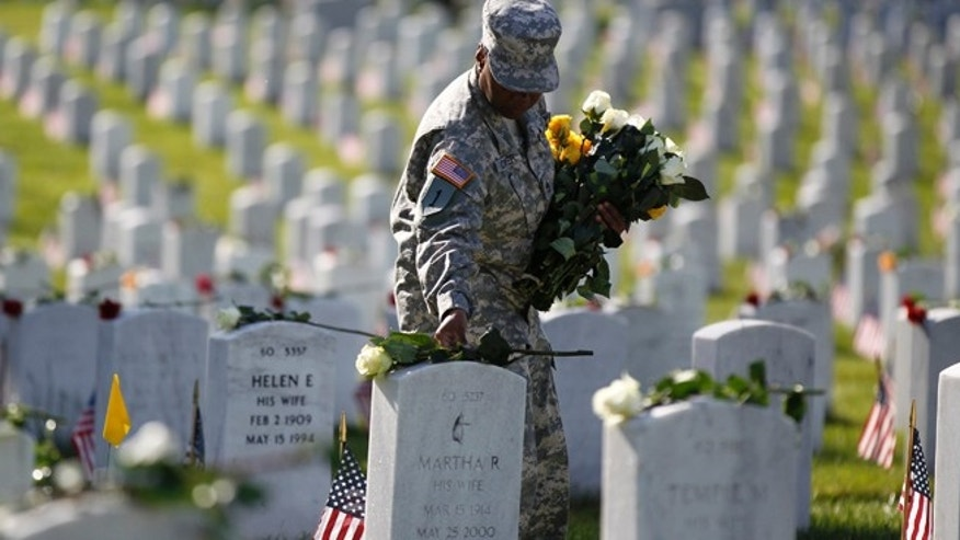 A soldier places roses on grave stones in Section 60 of Arlington National Cemetery.