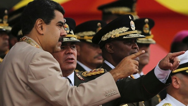 FILE - In this June 24, 2017 file photo, Venezuela's President Nicolas Maduro, left, talks to his Defense Minister Vladimir Padrino Lopez during Army Day celebrations at Fuerte Tiuna, in Caracas, Venezuela. Padrino Lopez challenged on Wednesday, July 19, 2017 the countries that have declared against the government's initiative to rewrite Venezuela's constitution, saying the nation will not submit to foreign governments. (AP Photo/Fernando Llano, File)